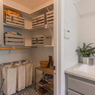Photo of a large classic utility room in Minneapolis with concrete flooring, a side by side washer and dryer, blue floors, a built-in sink, raised-panel cabinets, grey cabinets and yellow walls.