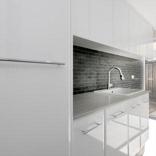 Exempel på en modern grå linjär grått tvättstuga enbart för tvätt, med en nedsänkt diskho, vita skåp, bänkskiva i koppar, svarta väggar, klinkergolv i porslin och grått golv