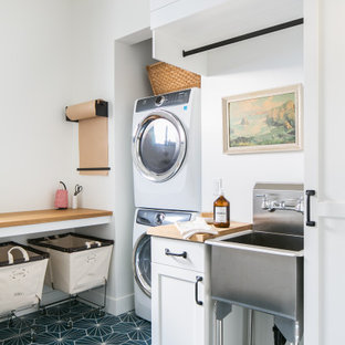 Beach style laundry room in Orange County with an utility sink, orange cabinets, wood benchtops, white walls, a stacked washer and dryer, blue floor and brown benchtop.