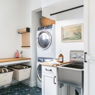 Réalisation d'une buanderie marine avec un évier utilitaire, des portes de placard oranges, un plan de travail en bois, un mur blanc, des machines superposées, un sol bleu et un plan de travail marron.