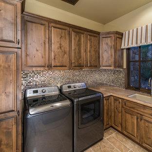 Idee per un'ampia sala lavanderia classica con lavello da incasso, ante con bugna sagomata, ante in legno scuro, top in legno, pareti beige, pavimento in travertino e lavatrice e asciugatrice affiancate