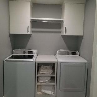 Esempio di una piccola sala lavanderia tradizionale con ante lisce, ante bianche, top in laminato, pareti grigie, pavimento in laminato, lavatrice e asciugatrice affiancate, pavimento marrone e top bianco