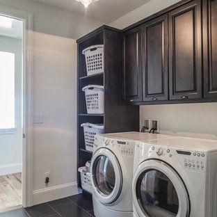 Dedicated laundry room - mid-sized industrial single-wall porcelain floor dedicated laundry room idea in Denver with raised-panel cabinets, gray walls and dark wood cabinets