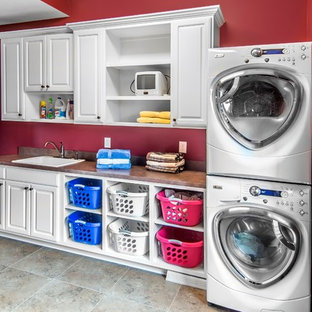 Design ideas for a mid-sized transitional single-wall dedicated laundry room in Omaha with raised-panel cabinets, white cabinets, laminate benchtops, red walls, porcelain floors, a stacked washer and dryer and a drop-in sink.