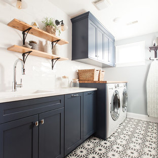 Mid-sized minimalist single-wall concrete floor and blue floor dedicated laundry room photo in Chicago with an undermount sink, shaker cabinets, blue cabinets, quartz countertops, blue walls, a side-by-side washer/dryer and white countertops