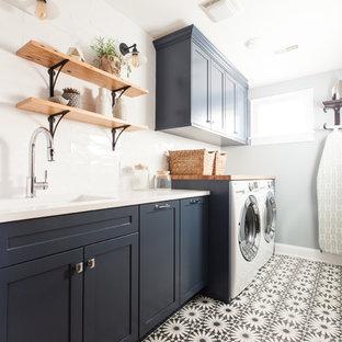 Ispirazione per una sala lavanderia minimalista di medie dimensioni con lavello sottopiano, ante in stile shaker, ante blu, top in quarzo composito, pareti blu, pavimento in cemento, lavatrice e asciugatrice affiancate, pavimento blu e top bianco