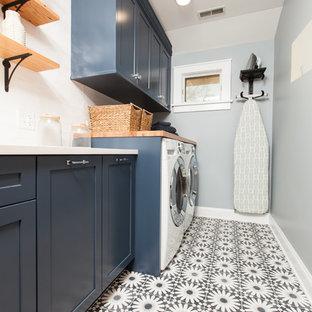 Foto på en mellanstor funkis vita linjär tvättstuga enbart för tvätt, med en undermonterad diskho, skåp i shakerstil, blå skåp, bänkskiva i kvarts, blå väggar, betonggolv, en tvättmaskin och torktumlare bredvid varandra och blått golv