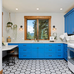 This is an example of a mid-sized country u-shaped dedicated laundry room in Denver with an undermount sink, shaker cabinets, blue cabinets, quartz benchtops, white splashback, ceramic splashback, ceramic floors, a side-by-side washer and dryer and white floor.