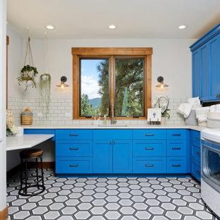 Foto di una sala lavanderia stile rurale di medie dimensioni con lavello sottopiano, ante in stile shaker, ante blu, top in quarzo composito, paraspruzzi bianco, paraspruzzi con piastrelle in ceramica, pavimento con piastrelle in ceramica, lavatrice e asciugatrice affiancate e pavimento bianco