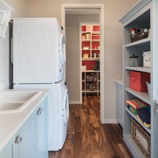 Immagine di una piccola lavanderia multiuso stile marinaro con lavello a doppia vasca, nessun'anta, ante blu, pareti grigie, pavimento in legno massello medio, lavatrice e asciugatrice a colonna e top bianco