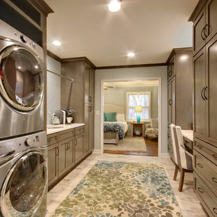 Utility room - huge traditional galley ceramic tile and gray floor utility room idea in Grand Rapids with an undermount sink, recessed-panel cabinets, gray cabinets, onyx countertops, a stacked washer/dryer and gray walls