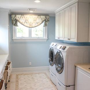 Immagine di una grande lavanderia multiuso stile shabby con lavello da incasso, ante bianche, pareti blu, pavimento con piastrelle in ceramica, lavatrice e asciugatrice affiancate e ante con bugna sagomata