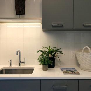 Свежая идея для дизайна: параллельная универсальная комната среднего размера в современном стиле с врезной раковиной, серыми фасадами, белым фартуком, фартуком из керамической плитки, белыми стенами, полом из керамогранита, со стиральной и сушильной машиной рядом, серым полом и белой столешницей - отличное фото интерьера