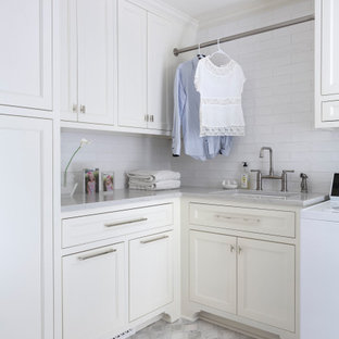 Inspiration for a transitional l-shaped dedicated laundry room in Little Rock with an undermount sink, recessed-panel cabinets, white cabinets, a side-by-side washer and dryer, grey floor and grey benchtop.