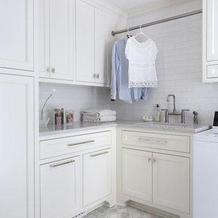 Idéer för att renovera en vintage grå l-formad grått tvättstuga enbart för tvätt, med en undermonterad diskho, luckor med infälld panel, vita skåp, en tvättmaskin och torktumlare bredvid varandra och grått golv