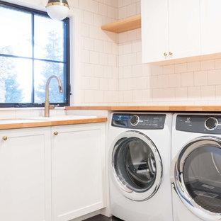 Idées déco pour une buanderie moderne avec un évier 1 bac, un placard à porte shaker, des portes de placard blanches, un plan de travail en bois, un sol en carrelage de porcelaine, le lave-linge et le sèche-linge forment un seul appareil électroménager et un sol gris.