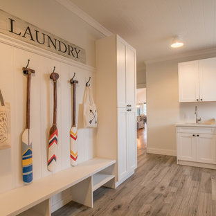 Design ideas for a large transitional l-shaped laundry room in Orange County with an undermount sink, shaker cabinets, white cabinets, solid surface benchtops, white walls, light hardwood floors and a side-by-side washer and dryer.