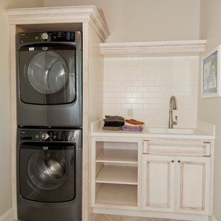 Inspiration for a mid-sized timeless single-wall porcelain floor dedicated laundry room remodel in Other with an integrated sink, white cabinets, solid surface countertops, beige walls, a stacked washer/dryer and recessed-panel cabinets