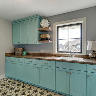 Design ideas for a mid-sized country galley dedicated laundry room in Minneapolis with a drop-in sink, flat-panel cabinets, turquoise cabinets, laminate benchtops, grey walls, porcelain floors, a side-by-side washer and dryer and multi-coloured floor.