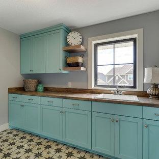 Foto på en mellanstor lantlig parallell tvättstuga enbart för tvätt, med en nedsänkt diskho, släta luckor, turkosa skåp, laminatbänkskiva, grå väggar, klinkergolv i porslin, en tvättmaskin och torktumlare bredvid varandra och flerfärgat golv