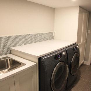 Modern inredning av en mellanstor linjär tvättstuga enbart för tvätt, med grå väggar, en nedsänkt diskho, luckor med infälld panel, vita skåp, bänkskiva i koppar, klinkergolv i keramik och en tvättmaskin och torktumlare bredvid varandra