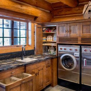 Exempel på en stor rustik l-formad tvättstuga enbart för tvätt, med en undermonterad diskho, luckor med infälld panel, skåp i mellenmörkt trä, granitbänkskiva, skiffergolv och en tvättmaskin och torktumlare bredvid varandra