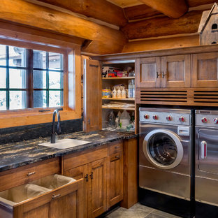 Dedicated laundry room - large rustic l-shaped slate floor dedicated laundry room idea in Chicago with an undermount sink, recessed-panel cabinets, medium tone wood cabinets, granite countertops and a side-by-side washer/dryer