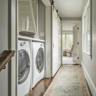 Bild på en liten lantlig linjär liten tvättstuga, med skåp i shakerstil, vita skåp, träbänkskiva, grå väggar och en tvättmaskin och torktumlare bredvid varandra