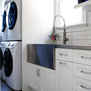 Example of a transitional single-wall gray floor dedicated laundry room design in Raleigh with a farmhouse sink, recessed-panel cabinets, white cabinets, stainless steel countertops, white walls, a stacked washer/dryer and gray countertops