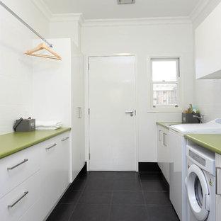 Immagine di una sala lavanderia minimalista di medie dimensioni con lavello da incasso, ante lisce, ante bianche, pareti bianche, pavimento con piastrelle in ceramica, top verde e top in laminato