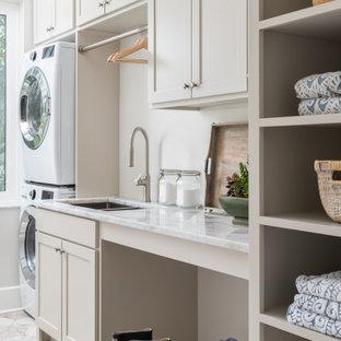 Ispirazione per una sala lavanderia country di medie dimensioni con lavello sottopiano, ante in stile shaker, ante beige, top in marmo, pareti bianche, pavimento in gres porcellanato, lavatrice e asciugatrice a colonna, pavimento beige e top bianco