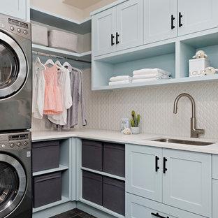 トロントのカントリー風おしゃれな洗濯室 (アンダーカウンターシンク、シェーカースタイル扉のキャビネット、青いキャビネット、上下配置の洗濯機・乾燥機、茶色い床、白いキッチンカウンター) の写真