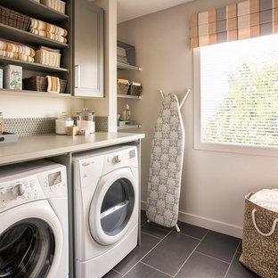Idéer för att renovera en vintage tvättstuga enbart för tvätt, med öppna hyllor, grå skåp, grå väggar, en tvättmaskin och torktumlare bredvid varandra och svart golv