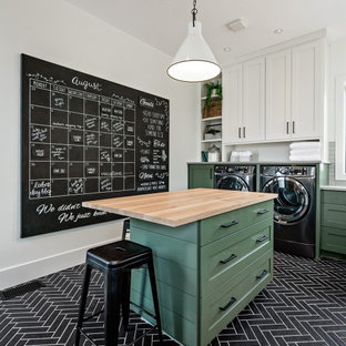 Idéer för att renovera ett lantligt grovkök, med skåp i shakerstil, gröna skåp, träbänkskiva, vita väggar, en tvättmaskin och torktumlare bredvid varandra och svart golv