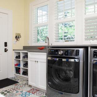 Immagine di una piccola lavanderia multiuso country con lavello sottopiano, ante lisce, ante bianche, top in cemento, pareti gialle, pavimento in cemento e lavatrice e asciugatrice affiancate