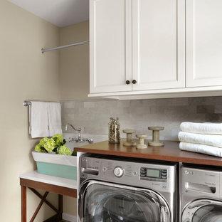 Inspiration för lantliga linjära brunt tvättstugor enbart för tvätt, med en rustik diskho, skåp i shakerstil, vita skåp, träbänkskiva, beige väggar, målat trägolv, en tvättmaskin och torktumlare bredvid varandra och flerfärgat golv