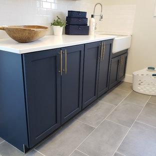 Amerikansk inredning av en liten vita parallell vitt tvättstuga enbart för tvätt, med en rustik diskho, luckor med infälld panel, blå skåp, bänkskiva i kvartsit, beige väggar, klinkergolv i keramik, en tvättmaskin och torktumlare bredvid varandra och grått golv