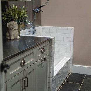Inredning av ett lantligt stort grovkök, med en enkel diskho, skåp i shakerstil, vita skåp, bänkskiva i rostfritt stål, beige väggar, klinkergolv i keramik, en tvättmaskin och torktumlare bredvid varandra och grått golv