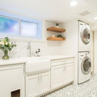Inredning av en lantlig mellanstor vita parallell vitt tvättstuga enbart för tvätt, med en rustik diskho, skåp i shakerstil, vita skåp, bänkskiva i kvarts, vita väggar, klinkergolv i porslin, en tvättpelare och grått golv