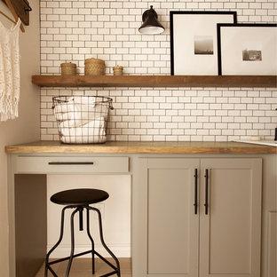 Bild på en mellanstor lantlig bruna brunt tvättstuga enbart för tvätt, med en rustik diskho, skåp i shakerstil, grå skåp, träbänkskiva, vita väggar, klinkergolv i keramik, en tvättmaskin och torktumlare bredvid varandra och grått golv