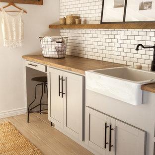 Lantlig inredning av en mellanstor bruna brunt tvättstuga enbart för tvätt, med en rustik diskho, skåp i shakerstil, grå skåp, träbänkskiva, vita väggar och en tvättmaskin och torktumlare bredvid varandra