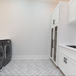 Large country dedicated laundry room in Chicago with an undermount sink, shaker cabinets, white cabinets, quartz benchtops, white splashback, mosaic tile splashback, white walls, porcelain floors, an integrated washer and dryer, grey floor and white benchtop.