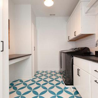 Idéer för en stor modern svarta parallell tvättstuga enbart för tvätt, med en undermonterad diskho, släta luckor, vita skåp, bänkskiva i kvarts, vitt stänkskydd, stänkskydd i tunnelbanekakel, vita väggar, klinkergolv i porslin, en tvättmaskin och torktumlare bredvid varandra och turkost golv