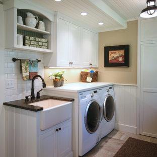 Bild på en liten lantlig linjär tvättstuga enbart för tvätt, med en rustik diskho, skåp i shakerstil, vita skåp, bänkskiva i koppar, beige väggar, en tvättmaskin och torktumlare bredvid varandra och beiget golv
