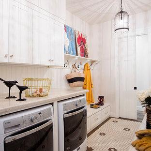 Lantlig inredning av ett beige parallellt beige grovkök, med skåp i shakerstil, vita skåp, vita väggar, målat trägolv, en tvättmaskin och torktumlare bredvid varandra och flerfärgat golv
