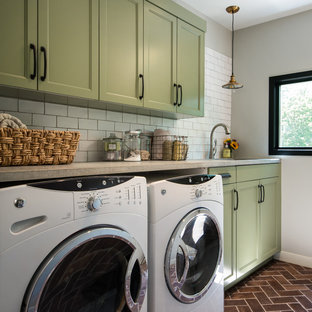 Mid-sized country single-wall dedicated laundry room in Chicago with an undermount sink, recessed-panel cabinets, green cabinets, concrete benchtops, grey walls, terra-cotta floors and a side-by-side washer and dryer.