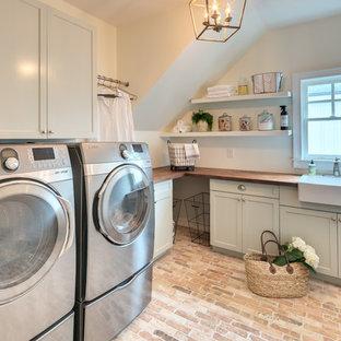 Inredning av en lantlig bruna l-formad brunt tvättstuga enbart för tvätt, med en rustik diskho, skåp i shakerstil, gröna skåp, träbänkskiva, vita väggar, tegelgolv, en tvättmaskin och torktumlare bredvid varandra och brunt golv