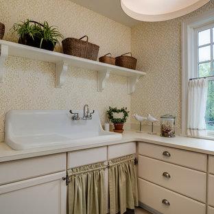 Immagine di una lavanderia stile shabby con ante beige, lavatoio e top beige