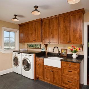 Inspiration för mellanstora lantliga linjära grovkök, med en rustik diskho, skåp i shakerstil, skåp i mellenmörkt trä, granitbänkskiva, beige väggar, skiffergolv och en tvättmaskin och torktumlare bredvid varandra