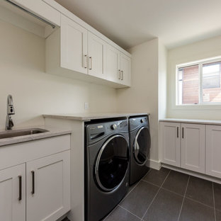 Photo of a large contemporary l-shaped separated utility room in Vancouver with a submerged sink, shaker cabinets, white cabinets, engineered stone countertops, white walls and a side by side washer and dryer.
